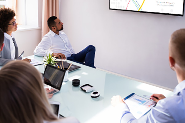 Five People in an office in front of a screen at a webinar.
